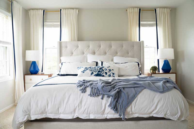 beautiful master bedroom upholstered bed with blue and white linens