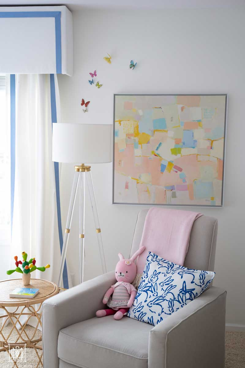 rocking chair glider in nursery with abstract artwork and white walls