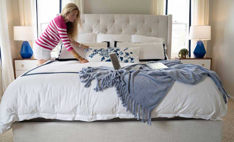woman making bed with blue and white bedding