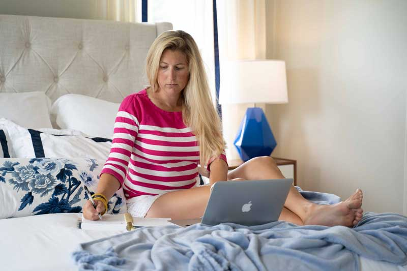 woman working on laptop on blue and white bed