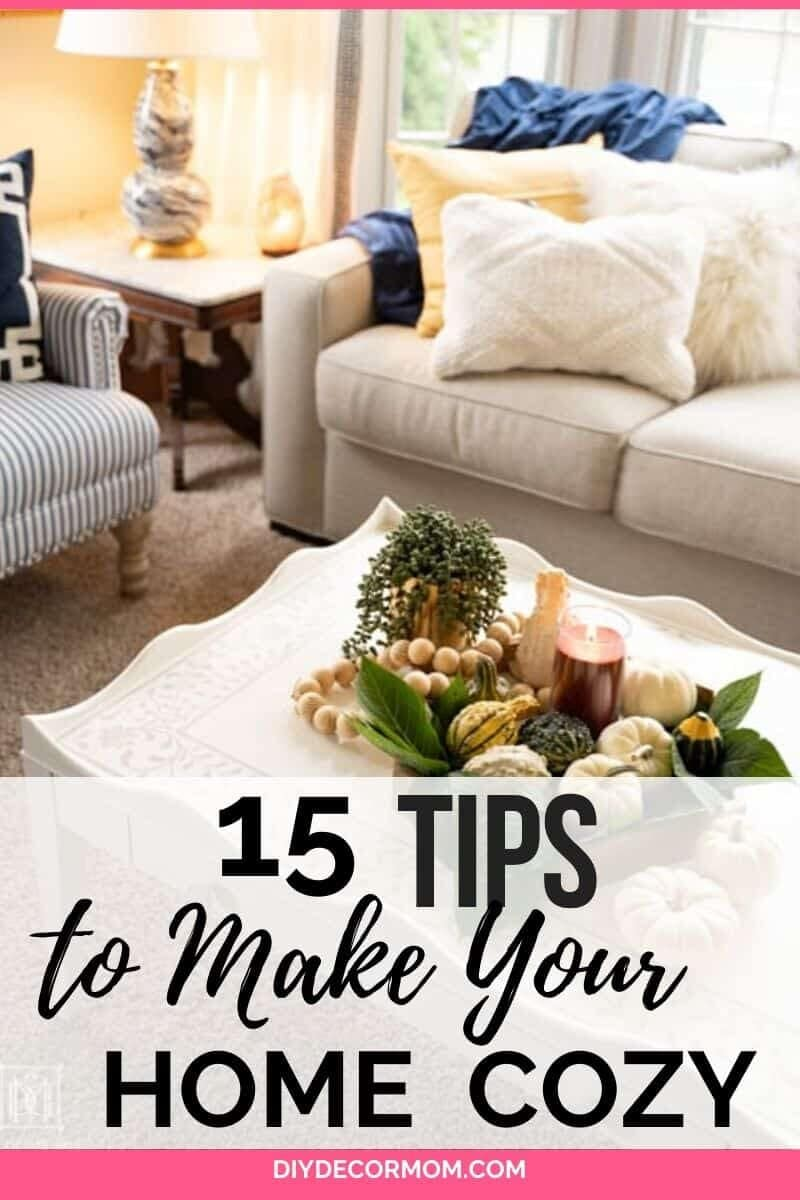 how to make your house cozy--picture of warm cozy vignette in family room with couch, pillows, lighted candles and blankets