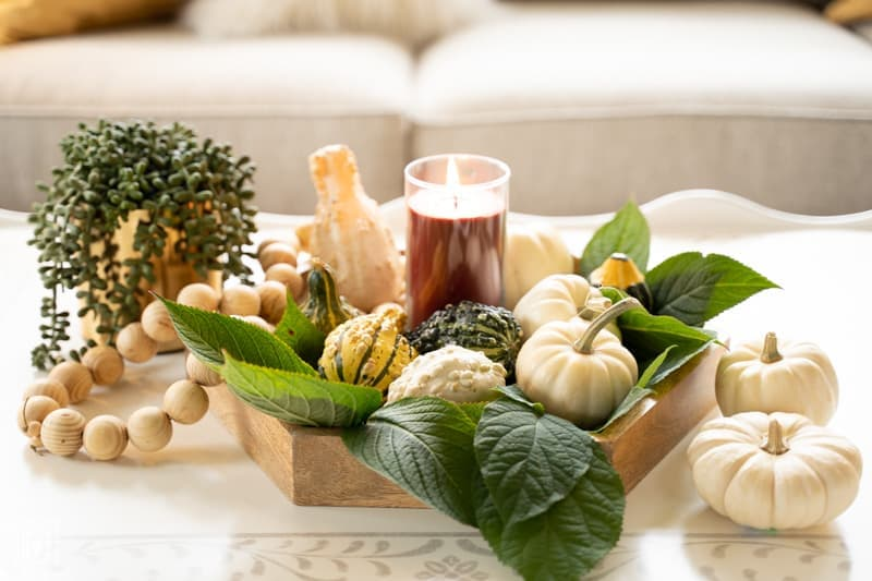 hygge in your home: picture of tray with fresh gourds and lighted candle