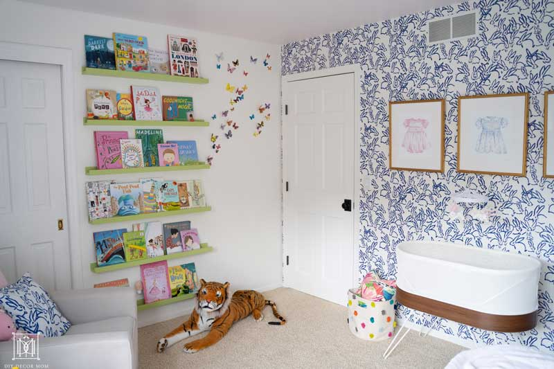 basinette and floating bookshelves in baby girl room with blue and white wallpaper