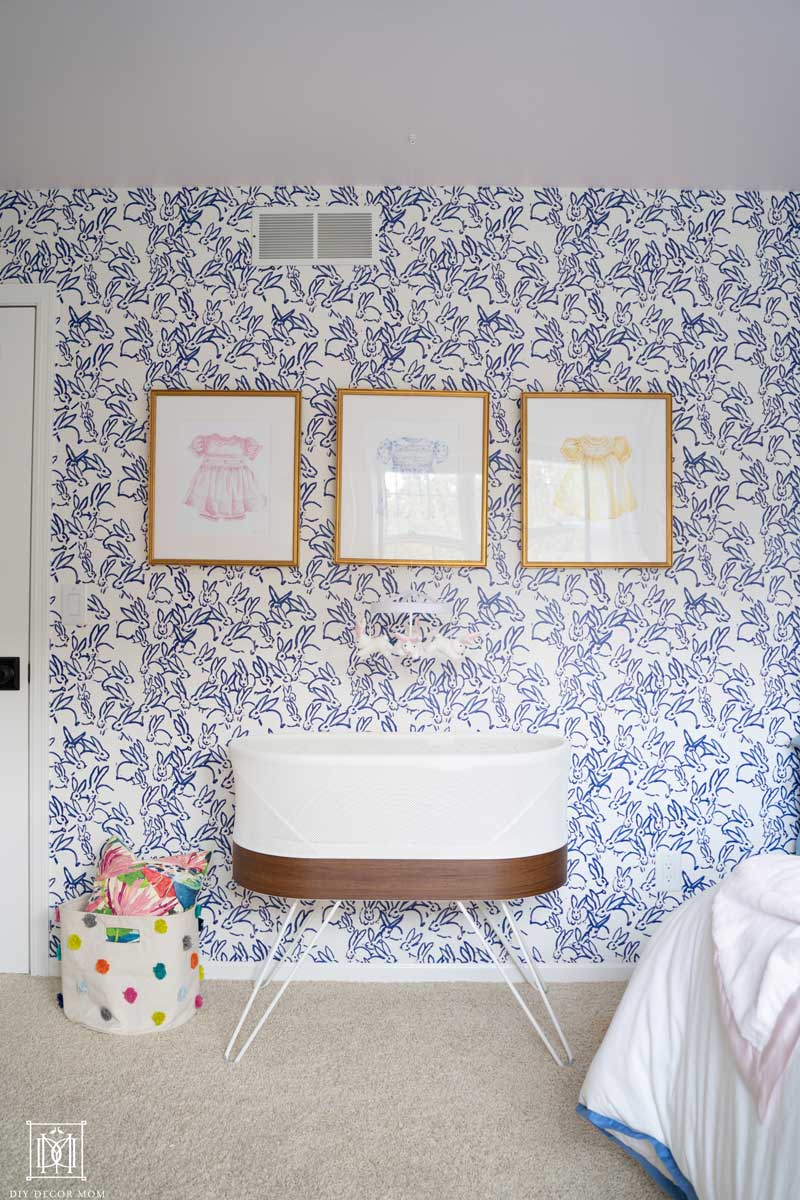 blue and white wallpaper accent wall in baby girl room with pink ceiling and pictures