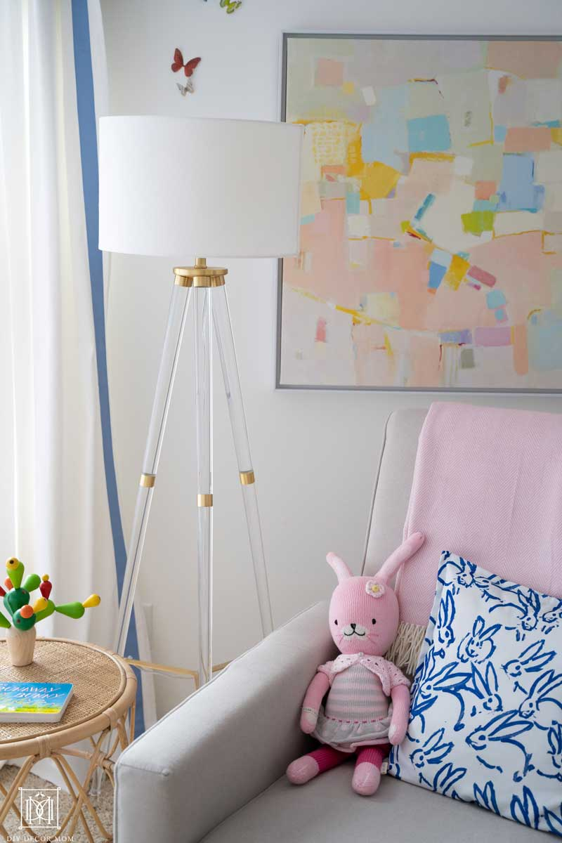 baby girl room decor with rocking chair and lucite lamp and abstract painting on white walls