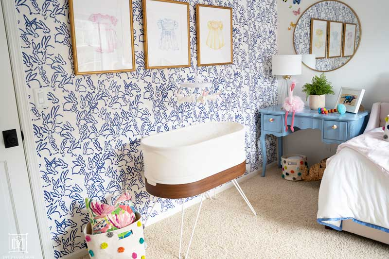 baby girl room decor- snoo in front of bunny wallpaper with blue and white