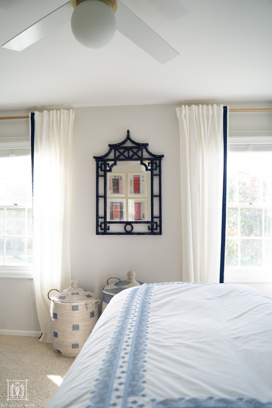 white curtains and white fan with gold touches in master bedroom with blue bamboo mirror and woven baskets