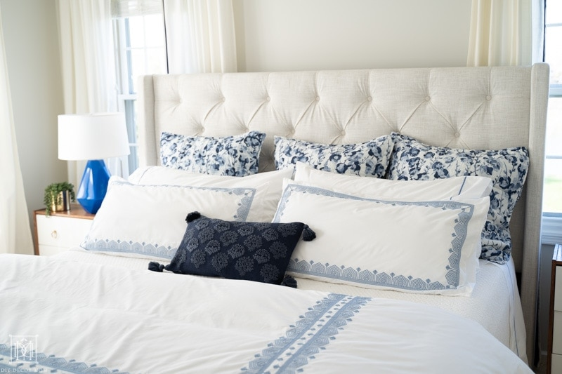 blue and white bedding on king size bed with duet cover, gray walls, and white curtains