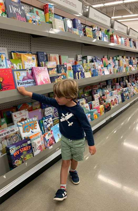 boy in aisle at meijer shopping for books