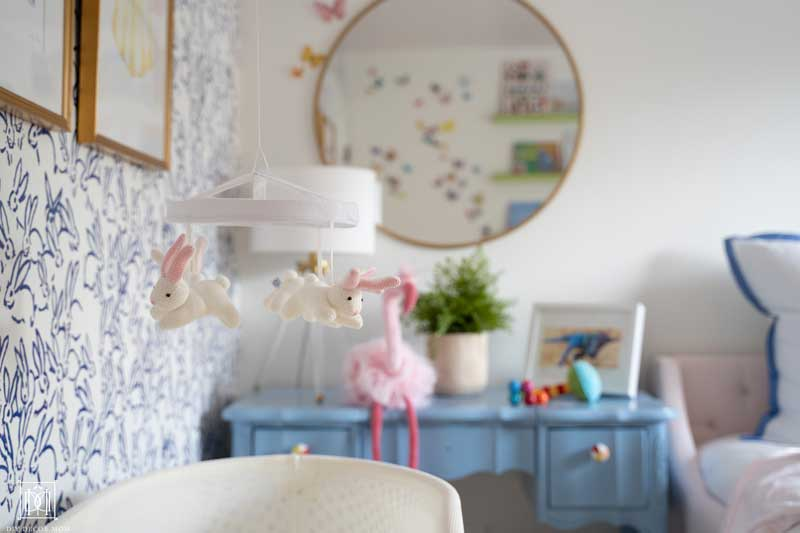 blue changing table with gold mirror and accent wallpaper in baby girl bedroom