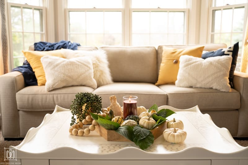 seasonal vignette with hygge tablescape and candles, natural textures, wood tones, and cozy pillows on couch