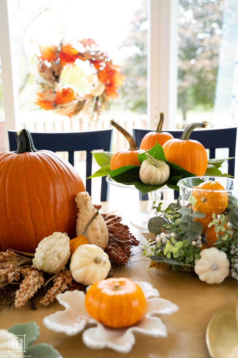 fall wreath over a fall tablescape with pumpkins