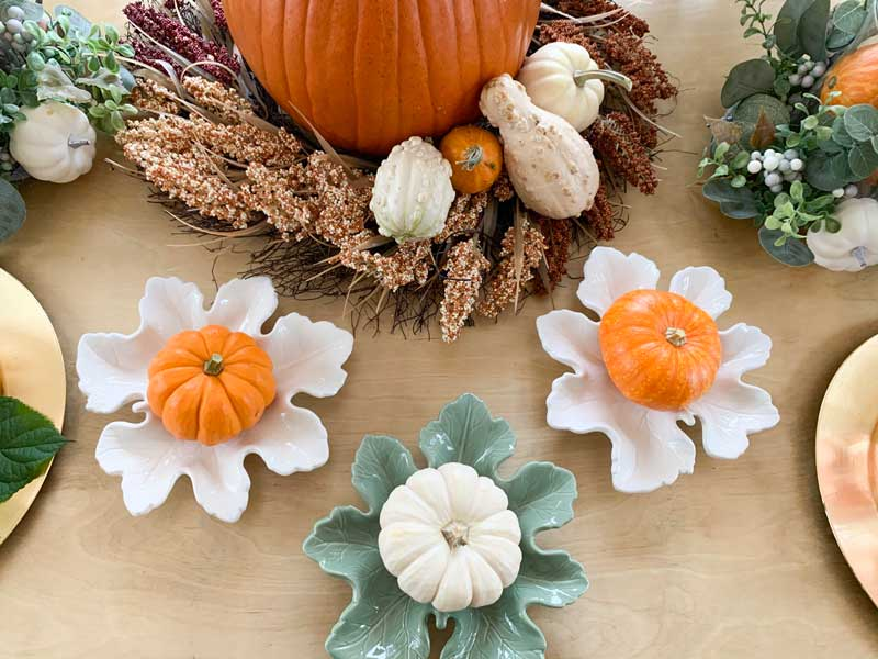 large pumpkin with wreath around it and small gourds