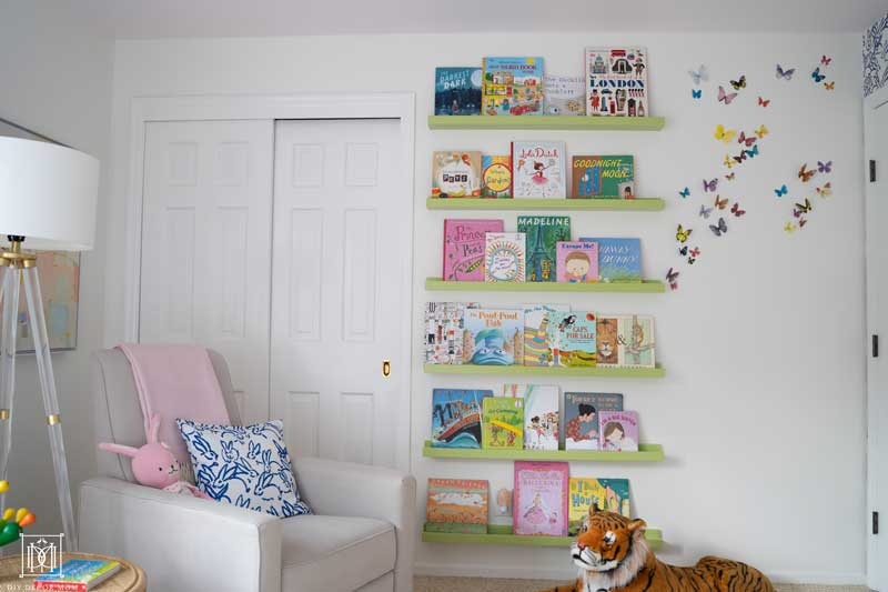 green floating bookshelves book ledge in white nursery with pink ceiling