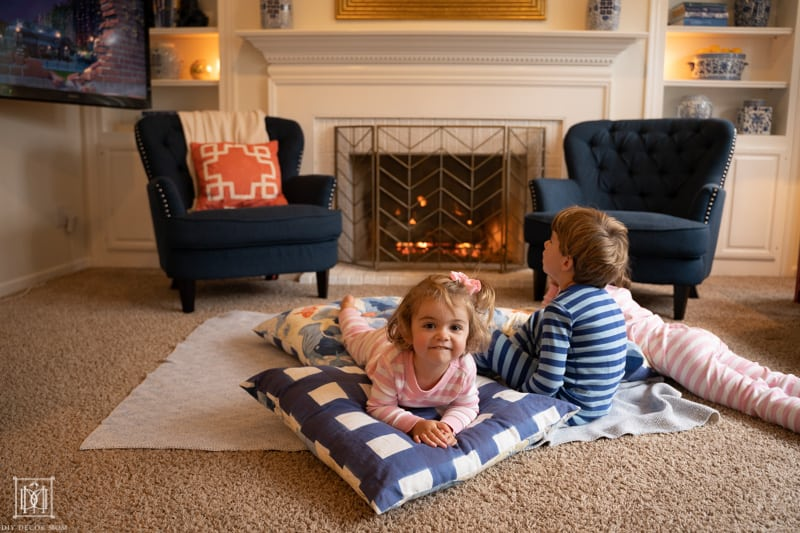 kids curled up in front of a fire watching a movie on floor pillows and a blanket--ways to increase your house hygge