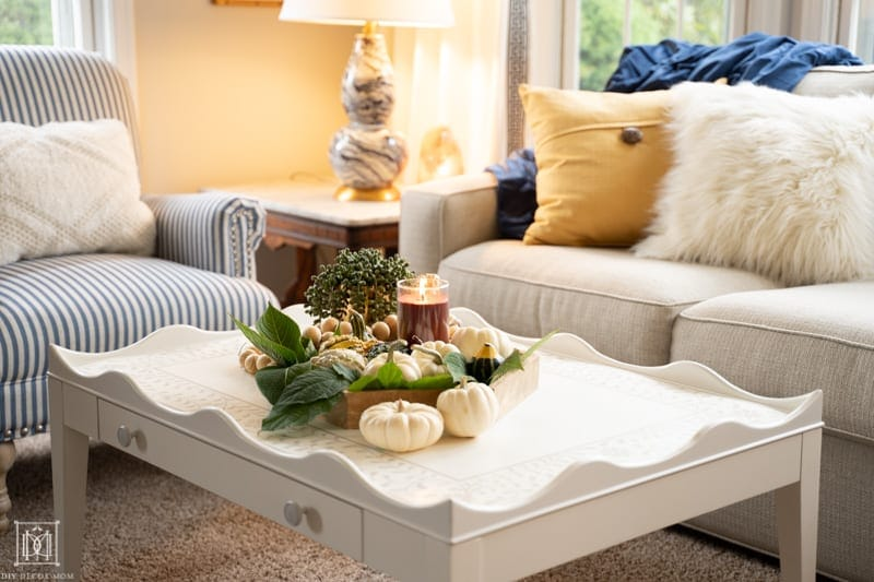 cozy picture of coffee table with candle burning on tray, warm lights, and soft furniture with fuzzy pillows--tips on making a cozy home