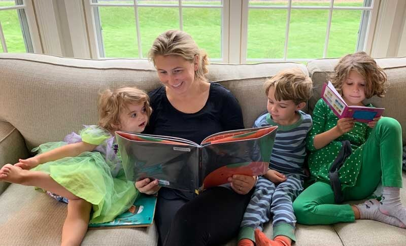mom reading a book to her three kids on a couch