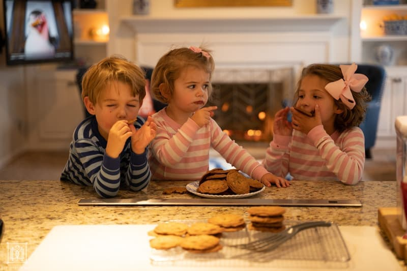 three siblings eating cookies at kitchen counter when one steals a cookie