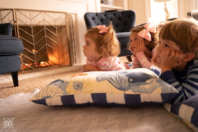 kids cozy by the fire watching a movie on a family movie night