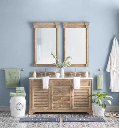 light blue bathroom with wood vanity and double mirror