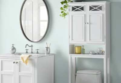 light blue bathroom with white vanity and oval mirror