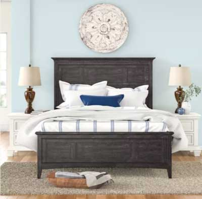 light blue painted bedroom with dark brown wood bed and medallion over the bed