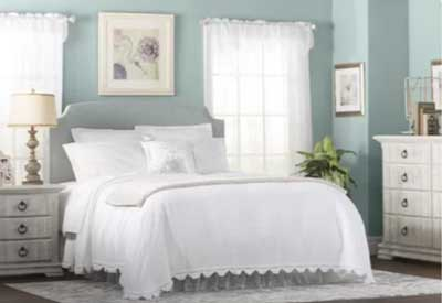 light blue painted bedroom with white bed and sheets