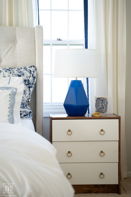 blue and white bedding in front of white curtains with modern bedside table and blue bedside table lamp
