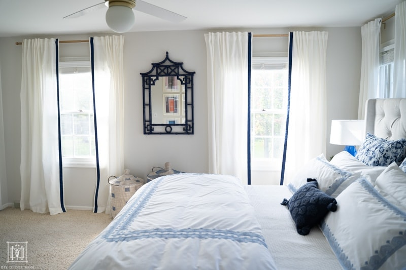 beautiful bedroom with blue and white bedding and white curtains