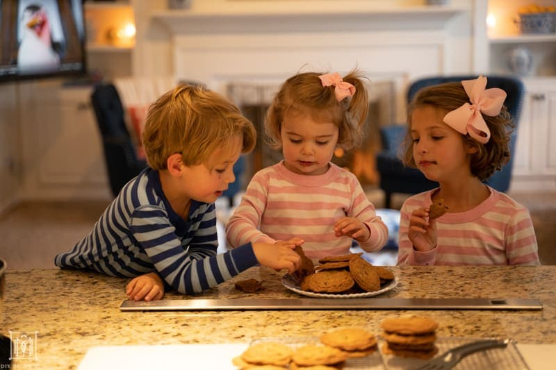 kids at kitchen counter eating warm baked chocolate chip cookies