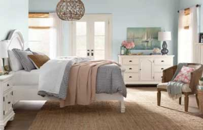 pale blue coastal bedroom with rattan light fixture and sisal rug and farmhouse furniture
