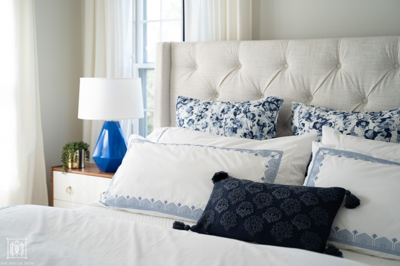 beautifully made blue and white bed with euro pillows on cream headboard, white curtains, and BM Classic Gray walls