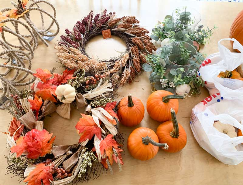 pumpkins and fall wreaths on table