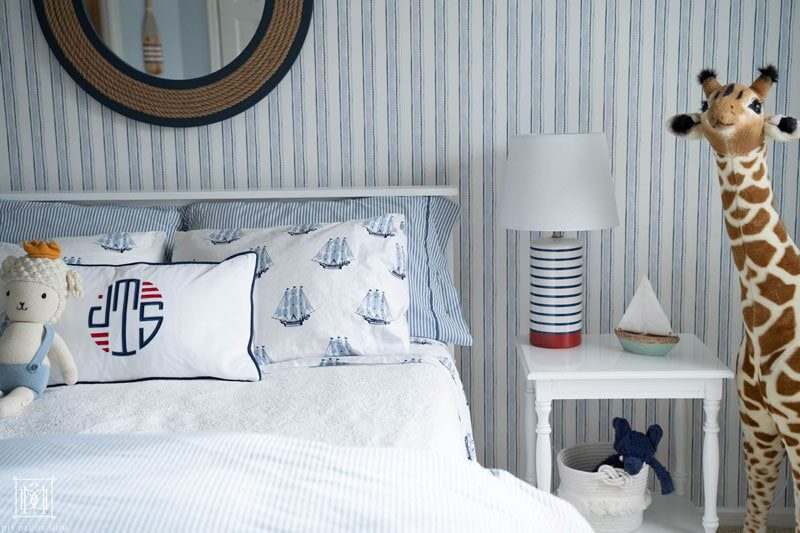 blue and white stripe wallpaper and nautical bedding in boys room