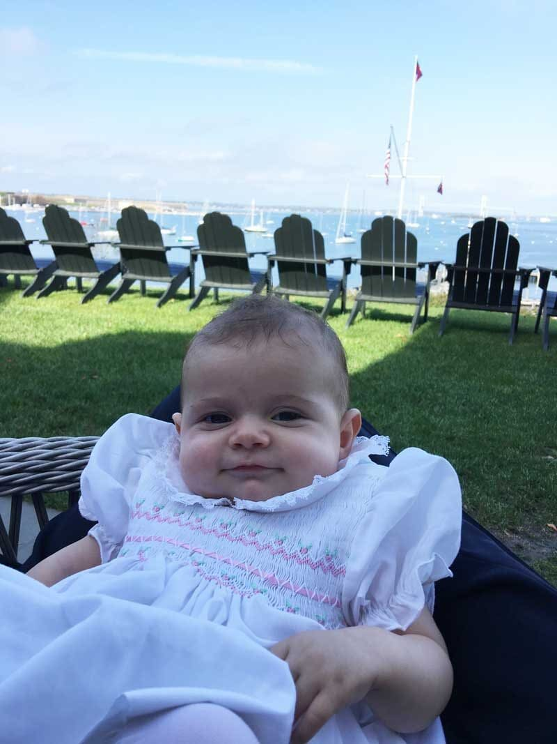 baby on dad's lap at yacht club overlooking harbor