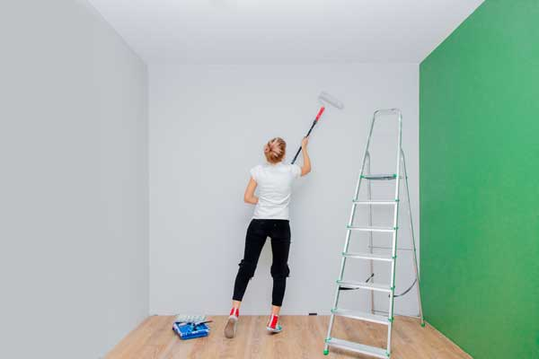 woman repainting a room before selling her house
