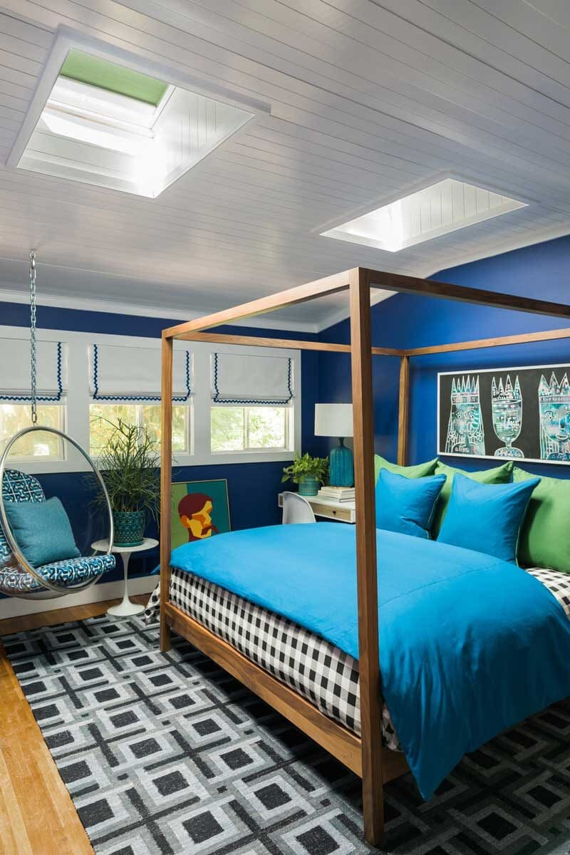 blue guest bedroom with skylights above help improve dark rooms