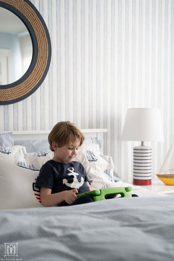 little boy sitting in bed and playing on tablet--see the best parent apps for screentime management