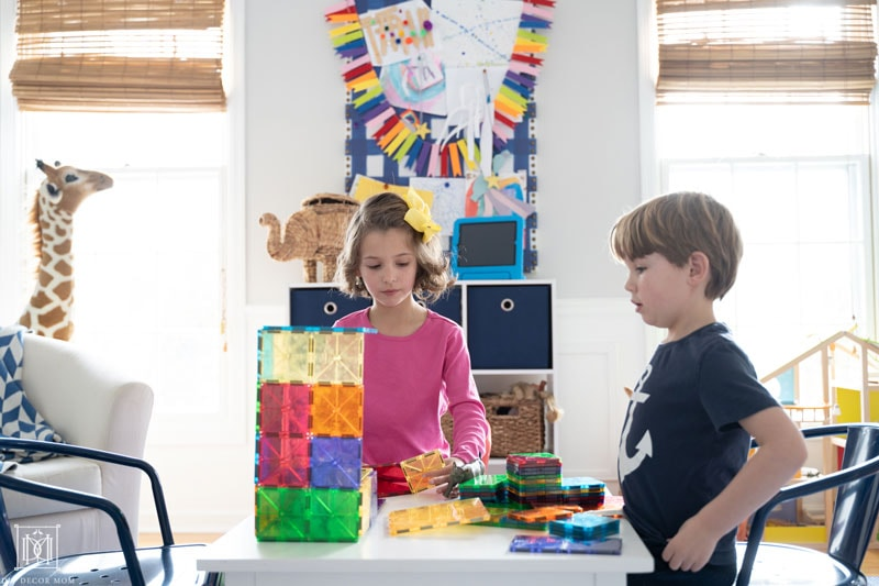 two kids playing building blocks and listening to audiobook in playroom