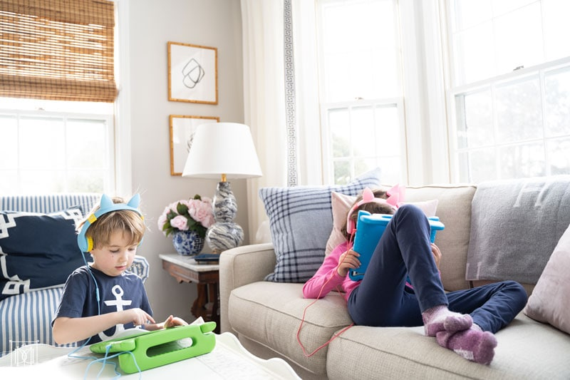 two kids reading and playing on ipads--see the best parents screen management for kids here