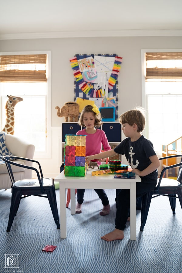 two kids in playroom playing magnatiles