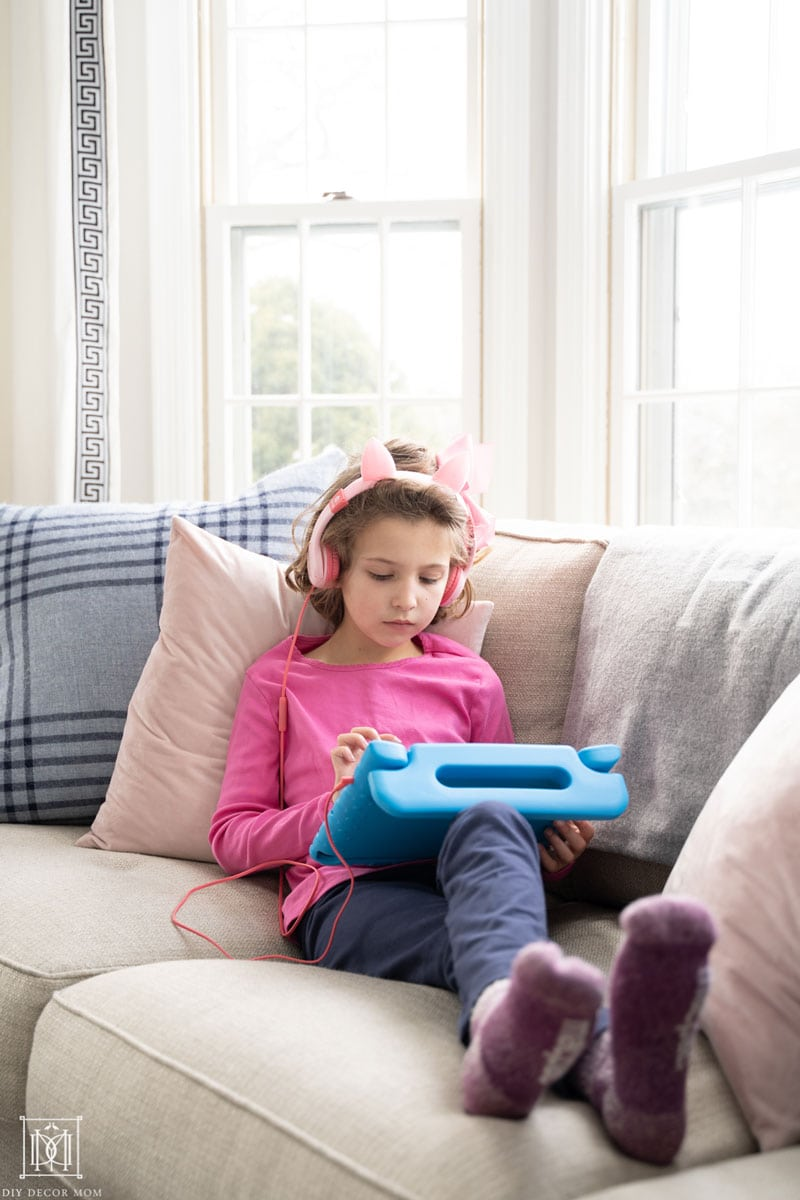 first grade girl reading on ipad on couch