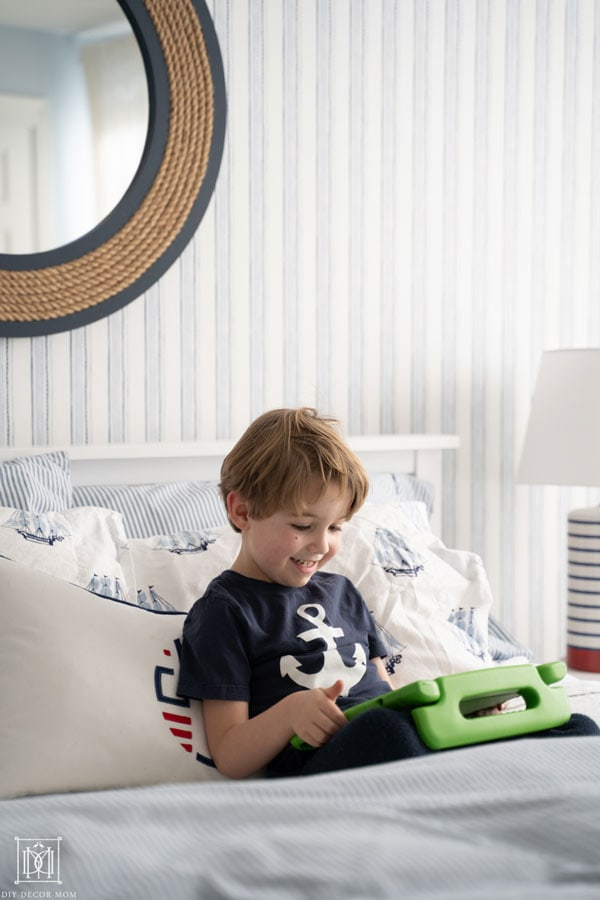 boy playing on ipad in bed