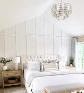 white paneling in master bedroom with comfy upholstered bed