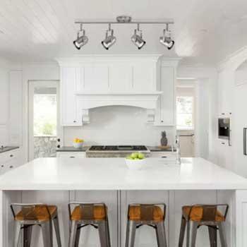 white kitchen range hood with wooden stools on island