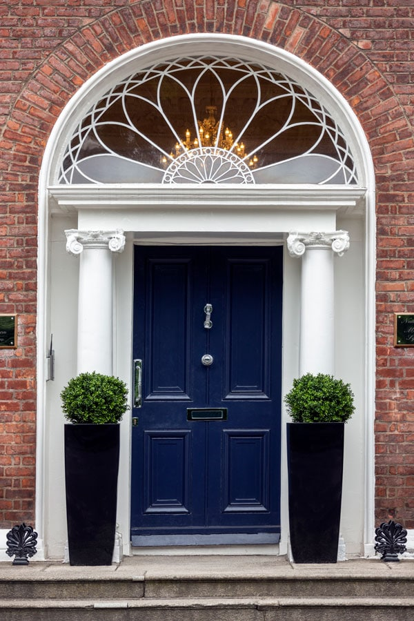 blue front door with brick exterior and two columns