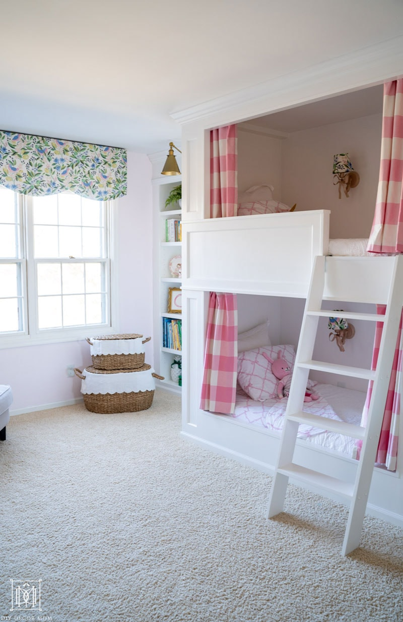 white built-in bunk beds with pink and white bedding and buffalo check curtains and scalloped window valance