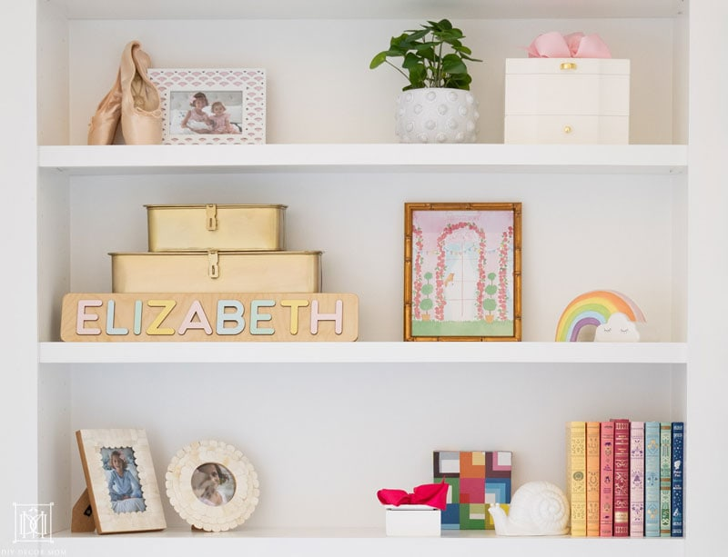 styled girls bedroom bookshelf with decorative objects