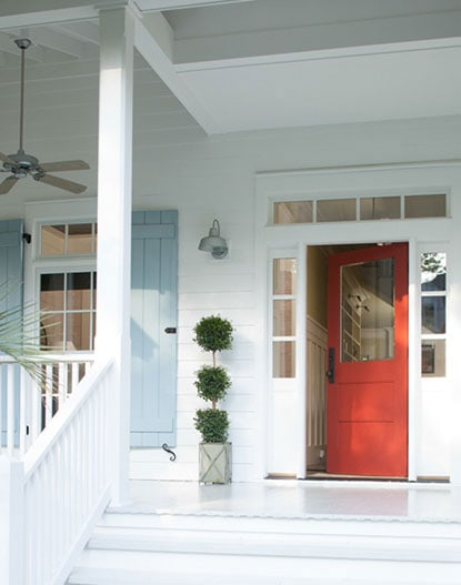 BM Raspberry Truffle front door with white siding and light blue shutters