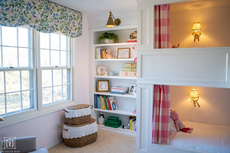 white bookcases with brass lighting in girls shared bunk room with toy storage in wicker baskets and scalloped pelmet box